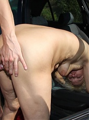 He bends her over the car seat and he fucks her while they're pulled over